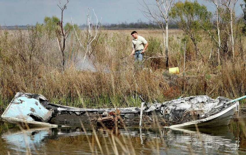 In this Feb. 16, 2011 photo, U.S. Department of Agriculture technician Kevin Balser burns a patch of prickly pear cacti near a destroyed boat on the bank of Cactus Canal in Jefferson Parish, La. The moth's larvae infest prickly pear cacti, and officials are trying to prevent them from spreading further west to Texas, where the infestation could explode.
