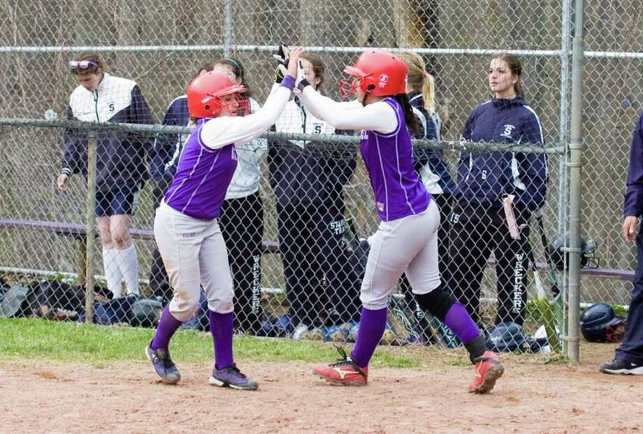 Westhill's Allie Souza, left, and Britt Horn celebrate their game winning runs after crossing the plate as Westhill High School hosts Staples in a softball game in Stamford, Conn., April 18, 2011. Photo: Keelin Daly / Stamford Advocate
