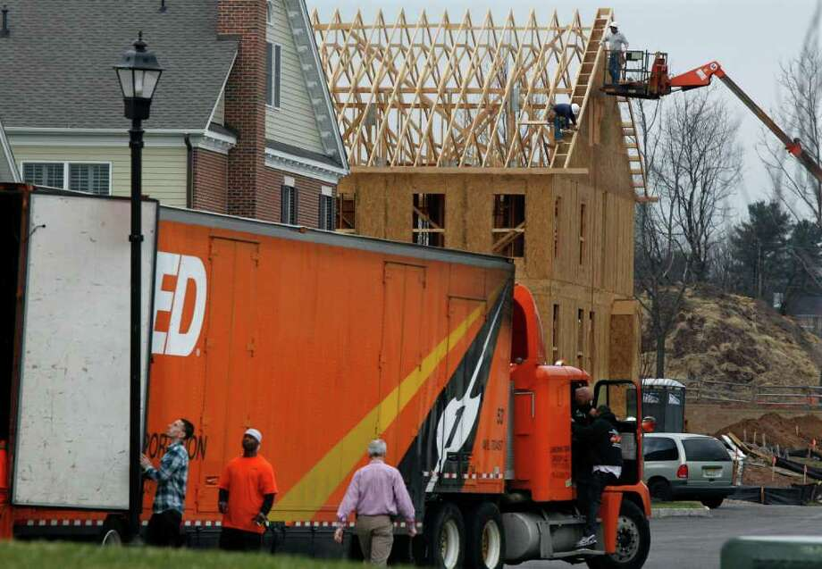 In this April 7, 2011 photo, construction continues on a new home in Newtown, Pa., as a moving van delivers furniture at a nearby finished home. Homebuilders are more pessimistic about the housing market this month, a dismal sign at the start of the spring-buying season. (AP Photo/Mel Evans) Photo: Mel Evans