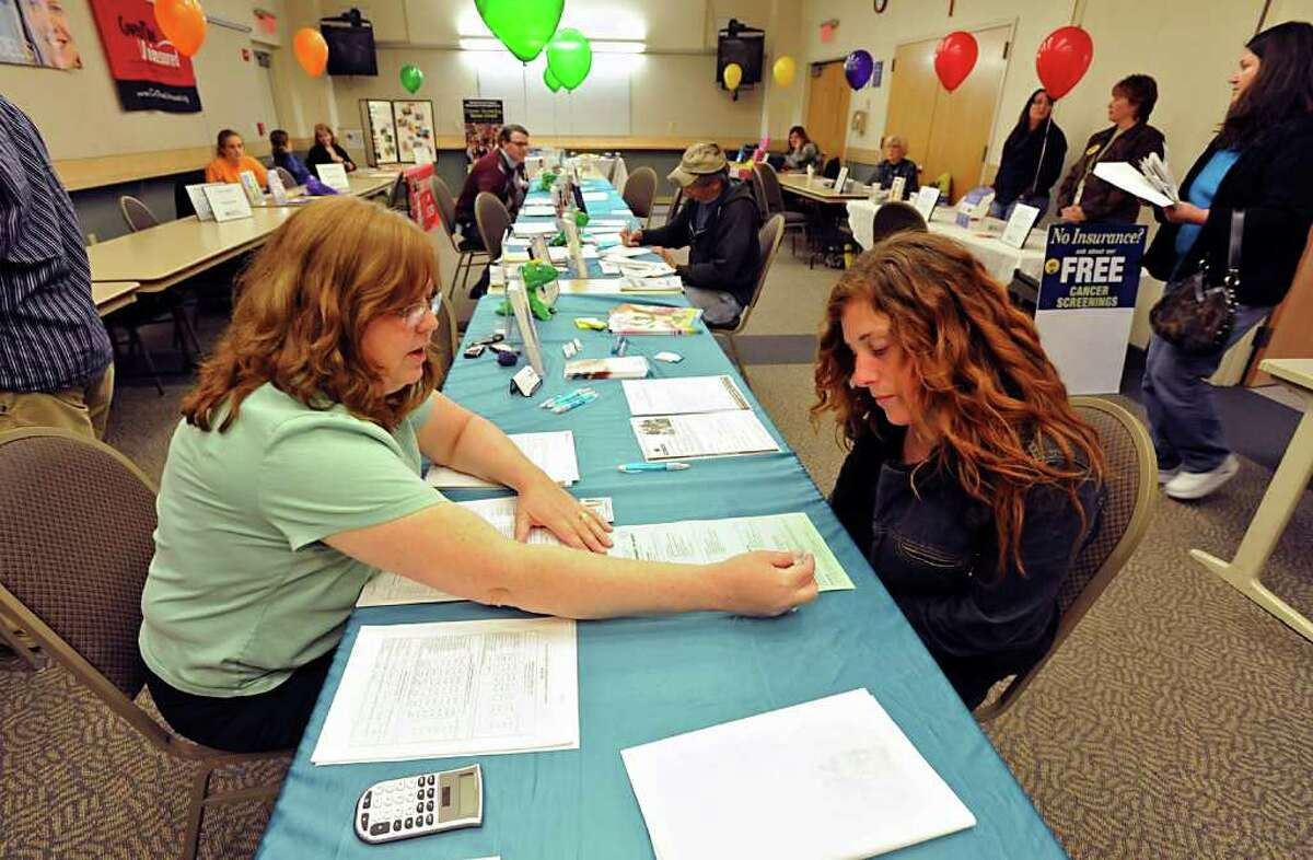 From left, Pam Cole of Fidelis Care helps Lisa Crounse of Mechanicville fill out forms for insurance at St. Mary's Seton Hospital in Troy, NY Monday April 18, 2011. Seton Health held an insurance enrollment event for people who do not have heatlth insurance(Lori Van Buren / Times Union)