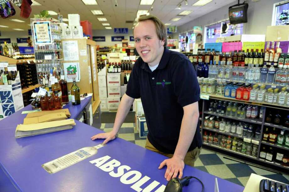 In this photo made April 6, 2011, Mark McNally is shown at his part-time job at a liquor store in Edina, Minn. McNally, 23, earned a history degree from the University of Minnesota and says he doesn't think he can earn the same kind of money his parents made when they were his age. (AP Photo/Jim Mone) Photo: Jim Mone