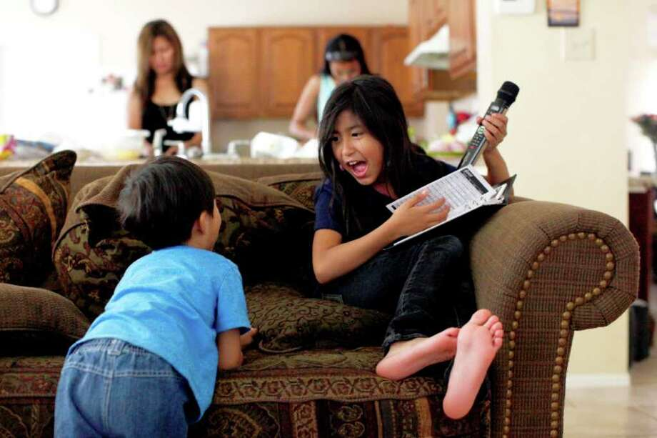 Julianna Perez, 7, sings karaoke while playing with her brother Uriah Perez, 3, while their mother, Lisa Perez (background left) and Maria Foster cook. Foster and Perez are Filipino. The Perez family moved to San Antonio about nine months ago. Photo: Lisa Krantz/Express-News / SAN ANTONIO EXPRESS-NEWS