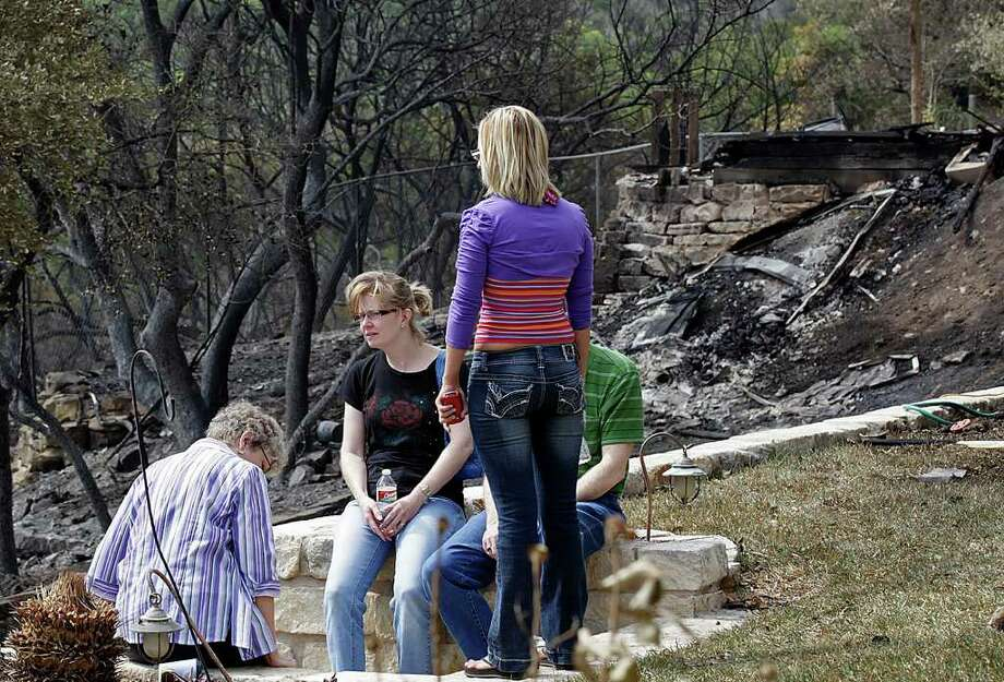 STATE – Kris Griffin, in black shirt and glasses, sits in her backyard with family members in the Oak Hills subdivision of West Austin, Monday, April 18, 2011. A 100-acres wildfire, is thought to have been started by a campfire at a homeless encampment Sunday morning, destroyed several homes. Her home was damage by the fire and compromise the roof structure. She was not allowed access to the inside due to safety issues. Michael Bernard Weathers, 60, has been charged with arson and is in the Travis County Jail on a $50,000 bail, according to the Austin American Statesman. JERRY LARA/glara@express-news.net Photo: JERRY LARA, San Antonio Express-News / SAN ANTONIO EXPRESS-NEWS