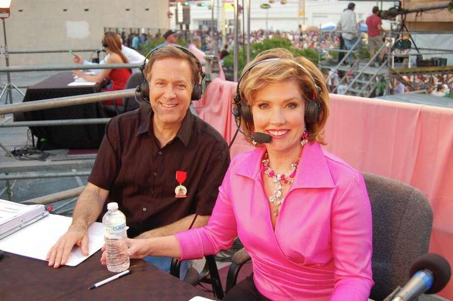 Hosts Randy Beamer and Deborah Knapp before the Fiesta Flambeau parade on Saturday.