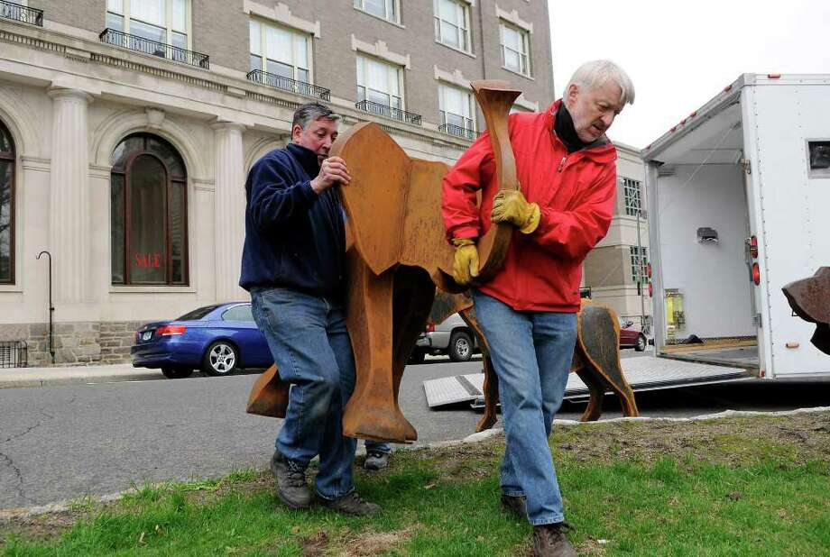 Denis Curtiss (in red), Kent, and Antonio Funseca, Stamford, carry an elephant sculpture to be displayed in front of the old town hall building on Greenwich Avenue, home to the Greenwich Arts Council, in Greenwich, CT on Tuesday, April 19, 2011. The installation is part of the Art to the Avenue project of the Greenwich Arts Council. The scuptures are the work of Curtiss. Photo: Shelley Cryan / Shelley Cryan freelance; Greenwich Time freelance