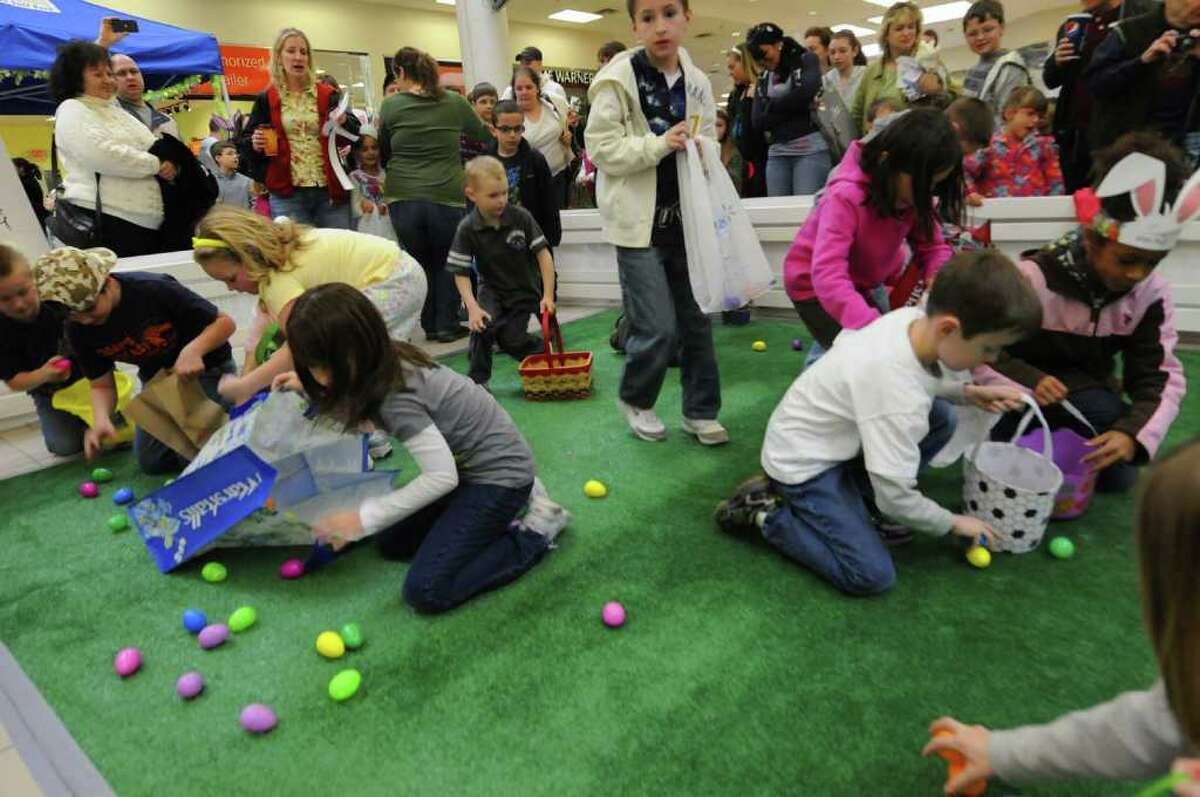 Children scramble for plastic eggs filled with candy during the Clifton Park Center Easter egg hunt on Saturday April 16,2011. ( Michael P. Farrell/Times Union )