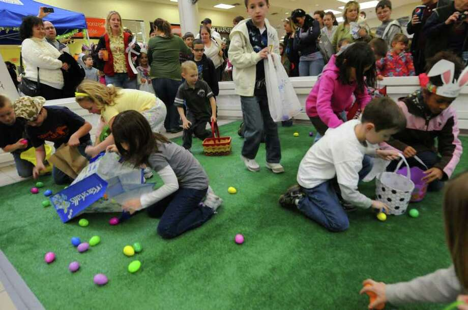 Children scramble for plastic eggs filled with candy during the Clifton Park Center Easter egg hunt on Saturday April 16,2011. ( Michael P. Farrell/Times Union ) Photo: Michael P. Farrell / 00012782A