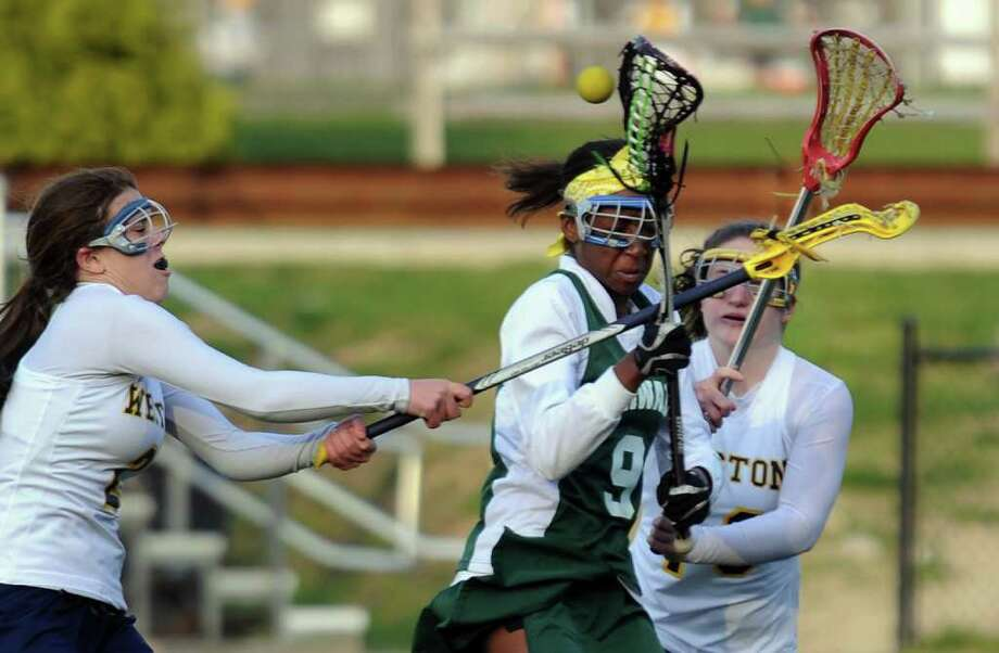 Highlights from girls lacrosse action between Norwalk and Weston in Weston, Conn. on Thursday April 14, 2011. Weston's #2 Morgan Moubayed, left, knocks the ball away from Norwalk's #9 Jasmine Pounds. Photo: Christian Abraham / Connecticut Post