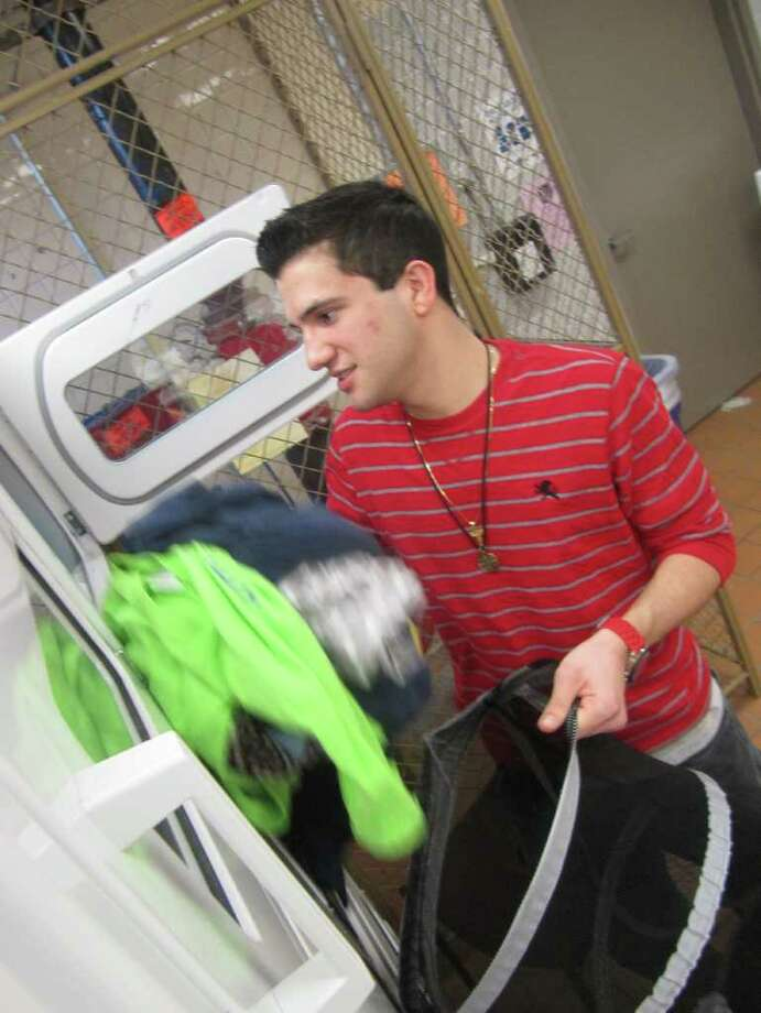 Fairfield University senior Joe Mercadante is seen on April 19 retrieving laundry from a dryer on the first floor of Regis Hall. LaundryView.com has helped make the chore of laundry a little easier, as students can tell when a machine is free, or their load done, from the comfort of their dorm room or anywhere else on campus, provided they have Internet access or a cell phone they can receive texts on. Photo: Kirk Lang / Fairfield Citizen