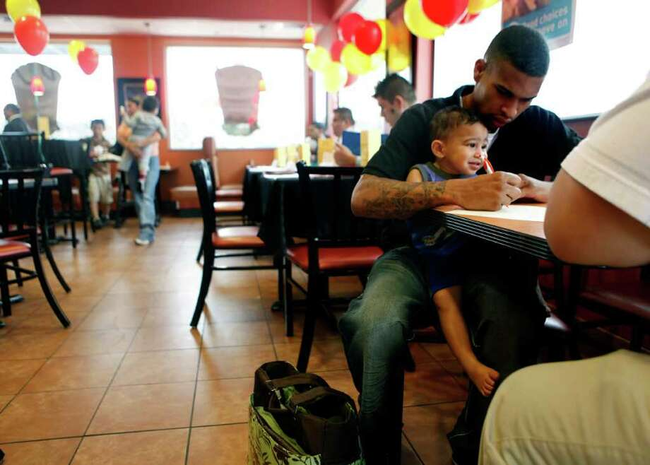 Robert Hamilton completes an application at the Potranco Road and Loop 1604 McDonalds restaurant while son Robert Hamilton, Jr., sits on his lap. Hamilton was partaking in the restaurant's national hiring day event. Locally, McDonalds was looking to fill 600 positions. Photo: WILLIAM LUTHER, SAN ANTONIO EXPRESS-NEWS / San Antonio Express-News