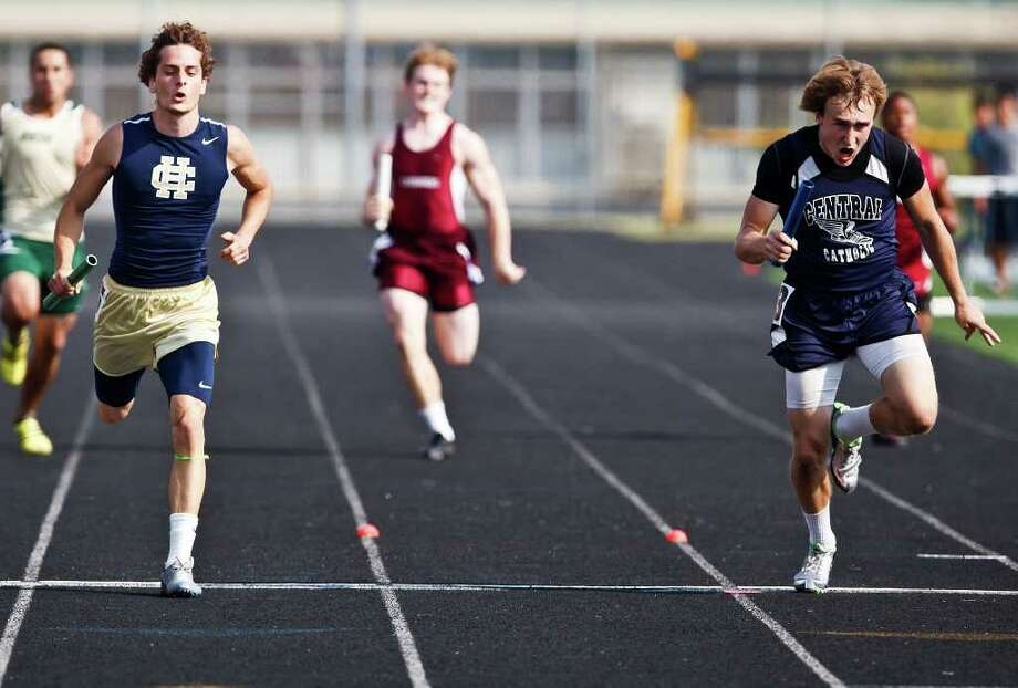 Central Catholic's Jake Tingle (right) beats Holy Cross' Sam Romero to the finish line by 0.003 seconds in the 800-meter relay during the TAPPS South Regional track and field meet on Tuesday, April 19, 2011. Photo: Marvin Pfeiffer/Special To The Express-News