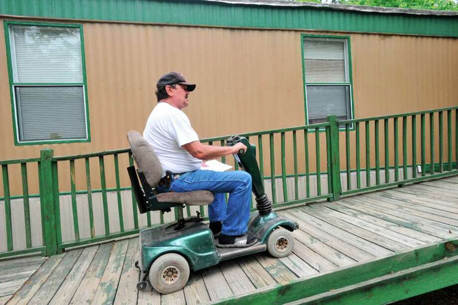 "Jon Nicholas uses an electric mobility scooter  to travel the wheelchair ramp to the back porch of his Lumberton mobile home. Nicholas has been told by State Farm his home insurance policy won't be renewed. That's because State Farm no longer wants to cover older mobile homes, but still will offer coverage for newer ""manufactured housing."" The termination of Mr. Nicholas' policy also means he's losing the discount he received for auto insurance because he had his policies ""bundled, "" meaning the insurer provided multiple products.   Tuesday, April 19, 2011.  Valentino Mauricio/The Enterprise   Valentino Mauricio/The Enterprise Photo: Valentino Mauricio / Beaumont"