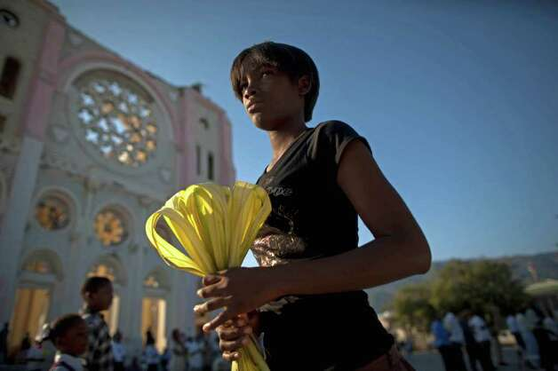 A woman holds her palm fronds in front of the once towering national cathedral before the start of Palm Sunday Mass in Port-au-Prince, Haiti, Sunday April 17, 2011. According to the New Testament, Palm Sunday marks the day Jesus rode into Jerusalem, greeted by cheering crowds bearing palm fronds. For Christians Palm Sunday marks the start of Holy Week. The week continues with commemorations of Jesus' crucifixion on Good Friday before celebrating his resurrection on Easter the following Sunday. Photo: AP