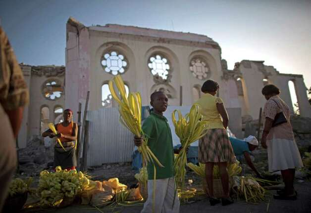 A young vendor sells palm fronds in front of the once towering national cathedral before the start of Palm Sunday Mass in Port-au-Prince, Haiti, Sunday April 17, 2011. According to the New Testament, Palm Sunday marks the day Jesus rode into Jerusalem, greeted by cheering crowds bearing palm fronds. For Christians Palm Sunday marks the start of Holy Week. The week continues with commemorations of Jesus' crucifixion on Good Friday before celebrating his resurrection on Easter the following Sunday. Photo: AP