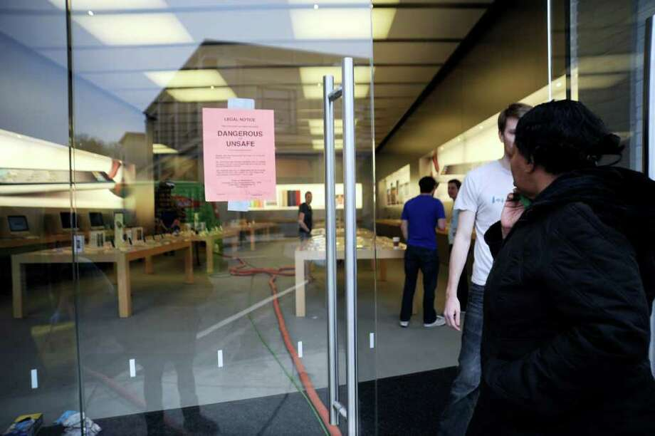 A woman looks a sign warning of unsafe conditions at on the Apple computer store on Greenwich Avenue on Wednesday, April 20, 2011.  The store was flooded Tuesday night when a cleaning crew damaged a sprinkler. Photo: Helen Neafsey / Greenwich Time
