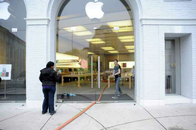 A woman comes to Apple on Greenwich Avenue to fix her iPhone Wednesday, finding that the store was closed, on April 20, 2011. The store was flooded Tuesday night when a cleaning crew damaged a sprinkler. Photo: Helen Neafsey / Greenwich Time