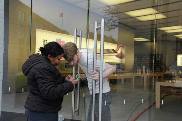 A woman came to Apple computer store on Greenwich Avenue to fix her iPhone Wednesday, finding help even though the store was close due to flooding, on April 20, 2011. The store was flooded Tuesday night when a cleaning crew damaged a sprinkler. Photo: Helen Neafsey / Greenwich Time