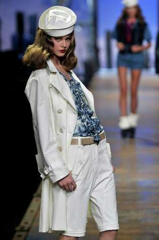 A model wears a Christian Dior look for spring and summer: a white trench over white knee-length shorts and a vibrant blue blouse with feminine cascading ruffles for a shot of color.