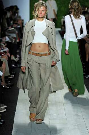 Michael Kors teams white tops with a neutral trench and matching wide leg trousers on teh left; on the right a bright green floor-lenght skirt is eye-catching with an optic white long-sleeved tee. Photo: X