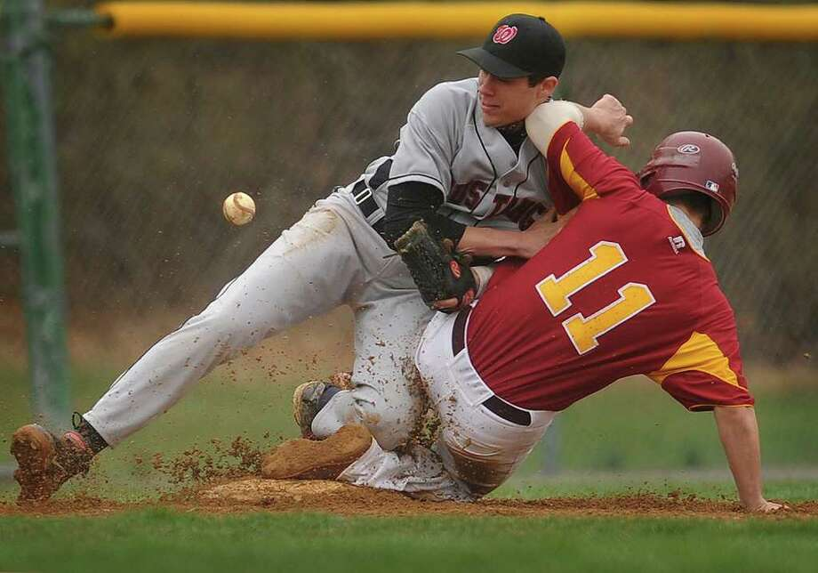The ball gets past Fairfield Warde third baseman Dario Pugliano as St. Joseph's Jerry Kramer slides into third during the first inning of their FCIAC matchup at St. Joseph High School in Trumbull on Wednesday, April 20, 2011. Photo: Brian A. Pounds / Connecticut Post