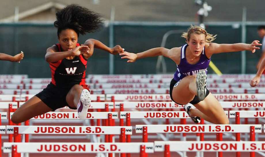 Wagner's Kayla Robinson (left) battles San Marcos' Amanda Hunt in the girl's 100-meter hurdles during the District 25-5A track and field meet at Rutledge Stadium on April 13, 2011.  Robinson won the event with a time of 15.12 and also won gold in the girls' 300-meter hurdles.   Photo by Marvin Pfeiffer Photo: Marvin Pfeiffer/Prime Time Newspapers
