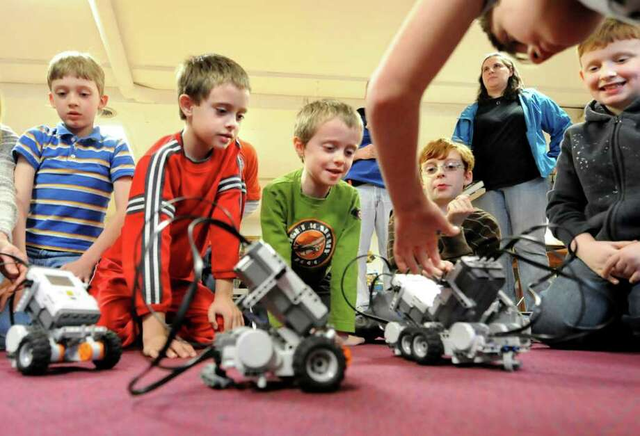 Children ages 7 and up watch their Lego robots move on the floor on Wednesday, April 20, 2011, at Ballston Spa Public Library in Ballston Spa, N.Y. The children learned to build and program the Lego robots in a workshop hosted by Bits, Bytes and Bots Computer Adventures. (Cindy Schultz / Times Union) Photo: Cindy Schultz