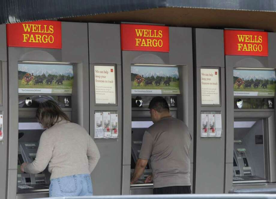 In this April 18, 2011 photo, customers use Wells Fargo Bank ATM machines in Santa Clara, Calif. Wells Fargo's first-quarter income jumped 51 percent as more people opened accounts with the bank and business customers took out loans. (AP Photo/Paul Sakuma) Photo: Paul Sakuma