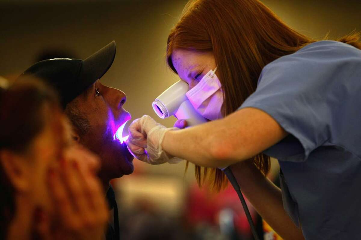 Dental hygiene student Audrey Rayniak gives an oral cancer screening to Kevin Smith at a free dental clinic on September 11, 2009 in Brighton, Colorado. (Getty Images)