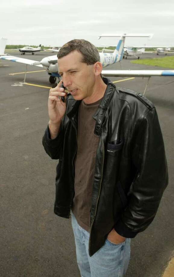 Commercial pilot Bill Phillips uses his cellphone on the tarmac at North Little Rock municipal Airport in North Little Rock, Ark., Wednesday, April 20, 2011. Phillips is representative of a trend of abandoning landline phones in favor of cellphones. (AP Photo/Danny Johnston) Photo: Danny Johnston