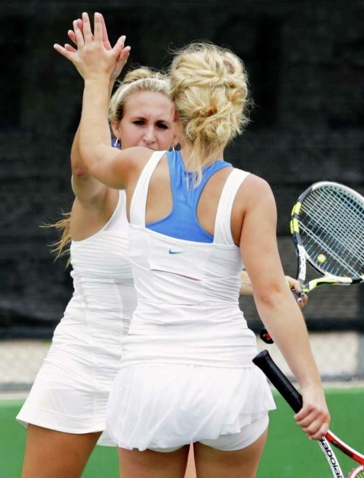 Sports daily - Sisters Courtney, left, and Haylie Wild slap hands after a point during the Girls Doubles against Judson in the Region IV-5A tennis tournament finals at McFarlin Tennis Center, Wednesday, April 20, 2011. Photo Bob Owen/rowen@express-news.net