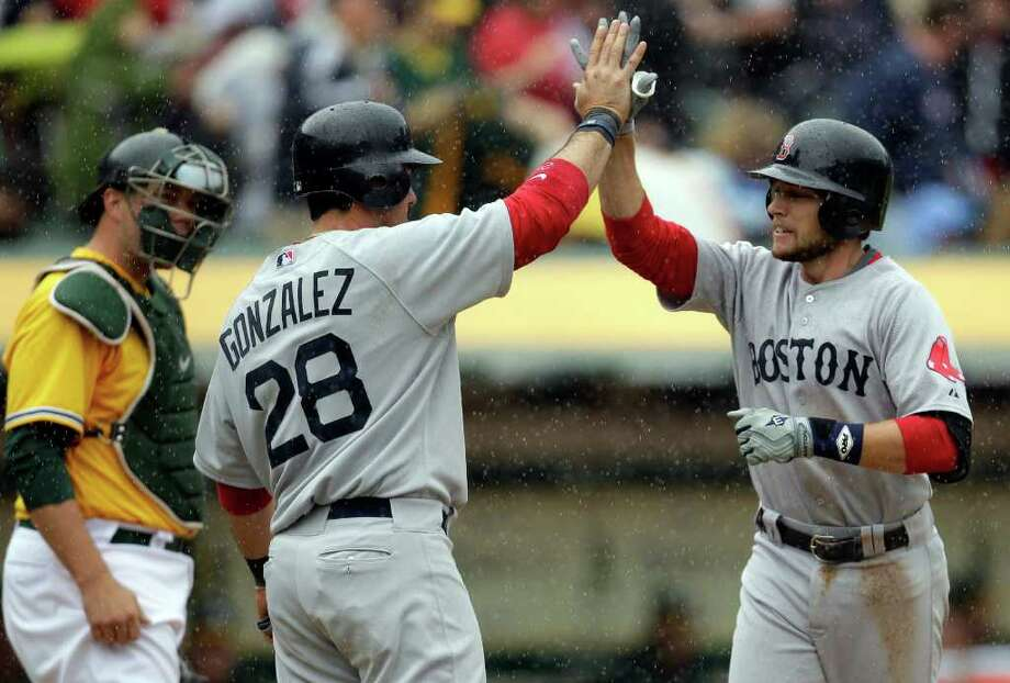 Boston Red Sox's Jed Lowrie, right, is congratulated by teammate Adrian Gonzalez after both scored on Lowrie's two-run home run off Oakland Athletics' Gio Gonzalez in the sixth inning of a baseball game, Wednesday, April 20, 2011, in Oakland, Calif. At left is A's catcher Landon Powell. (AP Photo/Ben Margot) Photo: Ben Margot