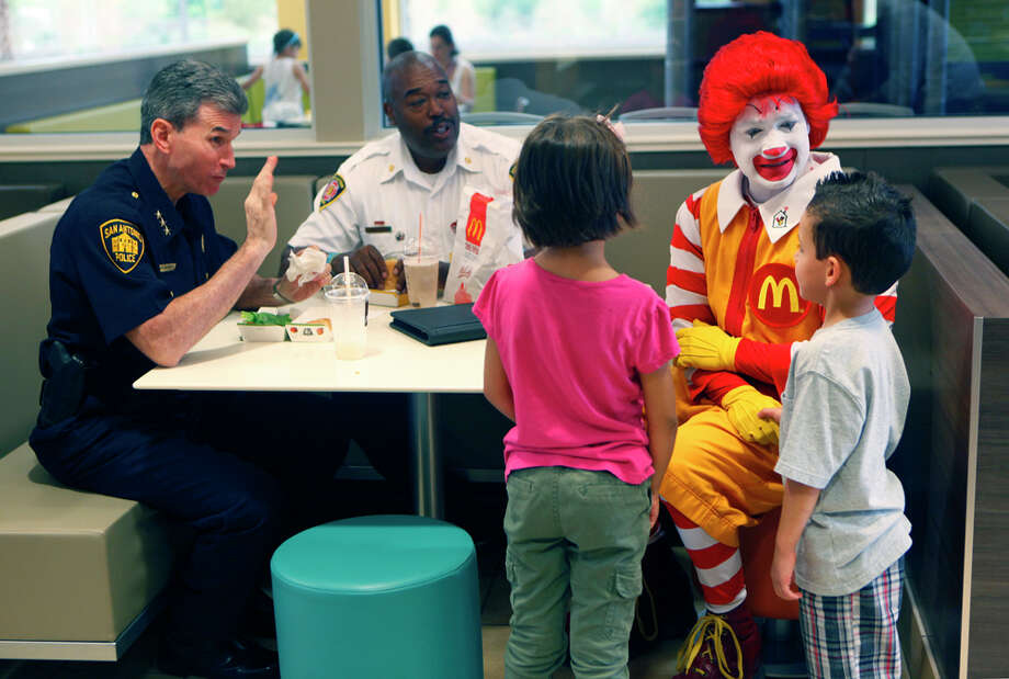 Police Chief William McManus (from left), Fire Chief Charles Hood and Ronald McDonald talk to 6-year-old cousins Isabel Fonseca (left) and Jayden Gonzalez. Photo: William Luther/Express-News / San Antonio Express-News