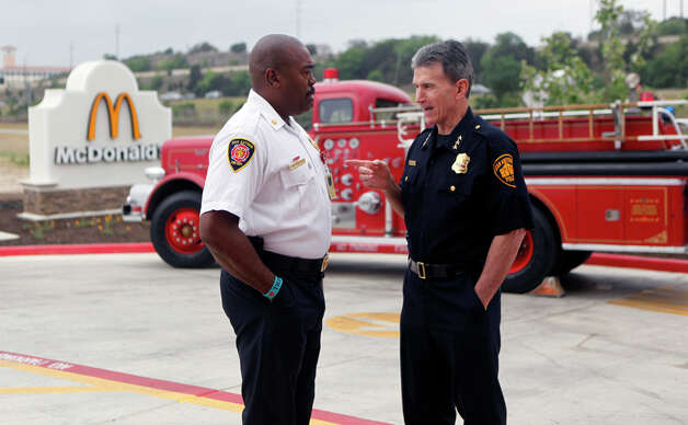 Fire Chief Charles Hood (left) and Police Chief William McManus talk Wednesday, April 20, 2011, outside the McDonald's at The Rim shopping center before a news conference in which McDonald's announced that it will donate a portion of all sales from 11a.m. to 2 p.m. on Friday, April 22, 2011, to the 100 Club of San Antonio. Photo: William Luther/Express-News / San Antonio Express-News