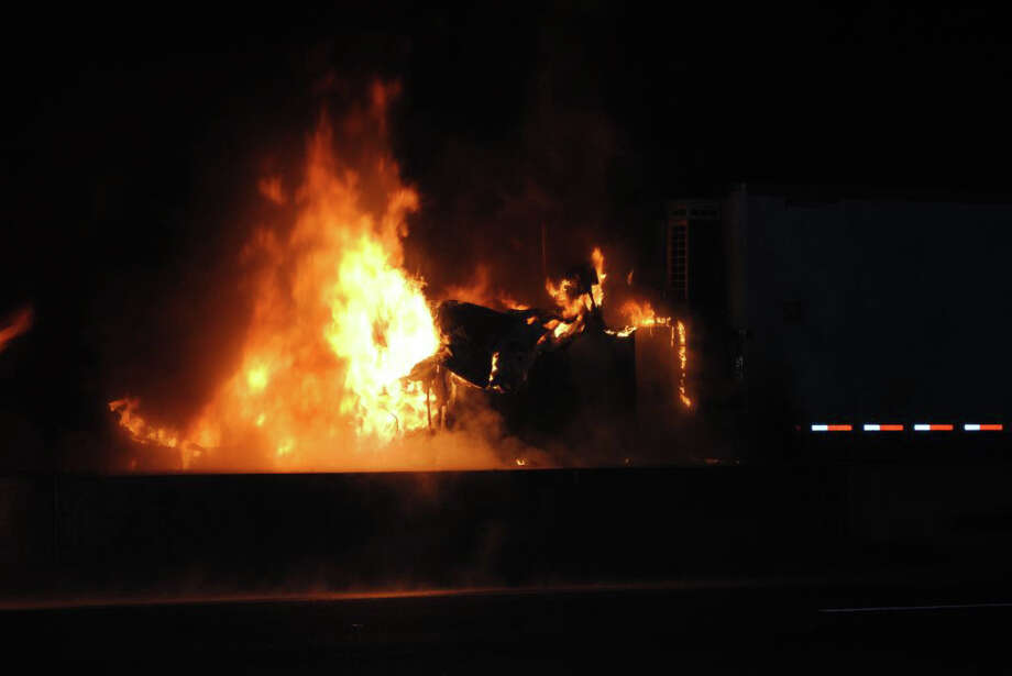 Flames ravage the cab of a tractor-trailer truck that collided with a car Wednesday night on Interstate 95 in Fairfield. Photo: Contributed Photo/Fairfield Fire Department / Fairfield Citizen contributed