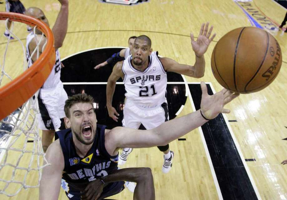Memphis Grizzlies' Marc Gasol, left, of Spain, shoots as San Antonio Spurs' Tim Duncan (21) looks on during the fourth quarter of Game 2 of a first-round NBA basketball playoff series on Wednesday, April 20, 2011, in San Antonio. Photo: AP