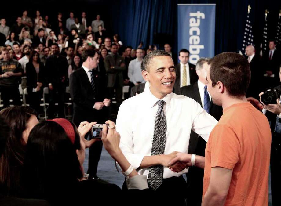 President Barack Obama shakes hands with a member of the audience at a town hall meeting to discuss reducing the national debt, Wednesday, April 20, 2011, at Facebook headquarters in Palo Alto, Calif. Photo: AP