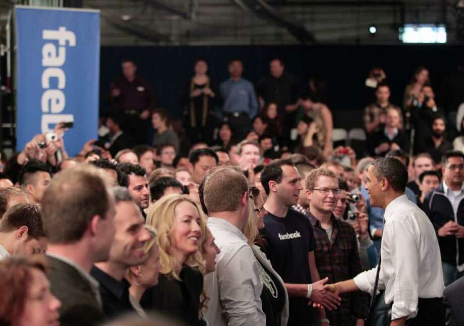 President Barack Obama shakes hands with members of the audience at a town hall meeting to discuss reducing the national debt, Wednesday, April 20, 2011, at Facebook headquarters in Palo Alto, Calif. Photo: AP