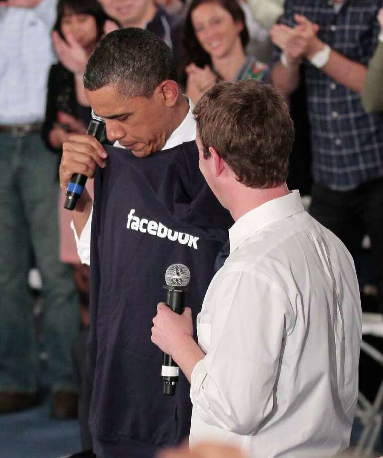 President Barack Obama holds up a Facebook hoodie sweater that was given to him by Facebook CEO Mark Zuckerberg, right, during a town hall meeting to discuss reducing the national debt, Wednesday, April 20, 2011, at Facebook headquarters in Palo Alto, Calif. Photo: AP