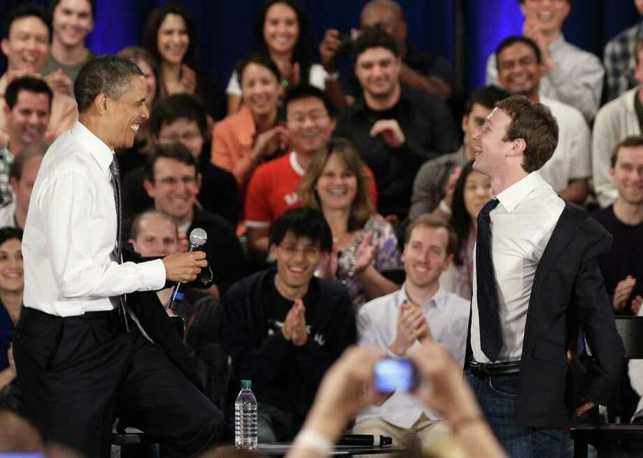President Barack Obama and Facebook CEO Mark Zuckerberg take off their jackets simultaneously during a town hall meeting at Facebook headquarters in Palo Alto, Calif., Wednesday, April 20, 2011. Photo: AP