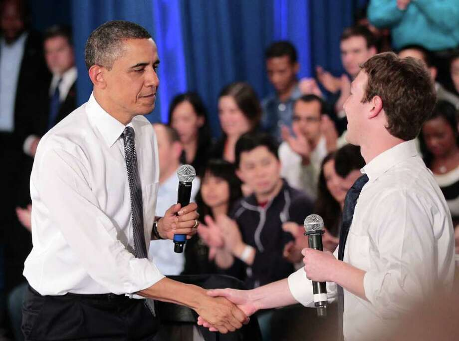 President Barack Obama shakes hands with Facebook CEO Mark Zuckerberg following their town hall meeting to discuss reducing the national debt, Wednesday, April 20, 2011, at Facebook headquarters in Palo Alto, Calif. Photo: AP