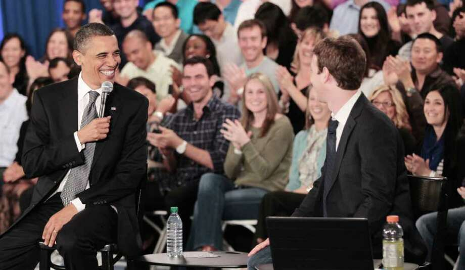 President Barack Obama laughs with Facebook CEO Mark Zuckerberg during a town hall meeting to discuss reducing the national debt , Wednesday, April 20, 2011, at Facebook headquarters in Palo Alto, Calif. Photo: AP