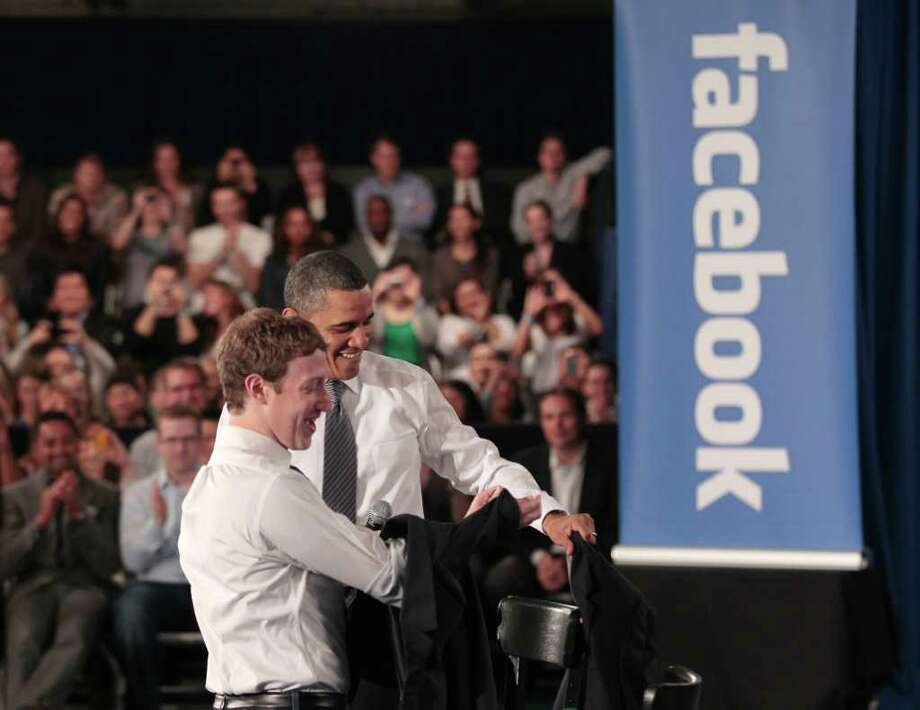 President Barack Obama and Facebook CEO Mark Zuckerberg take off their jackets before the start of their town hall meeting to discuss reducing the national debt, Wednesday, April 20, 2011, at Facebook headquarters in Palo Alto, Calif. Photo: AP