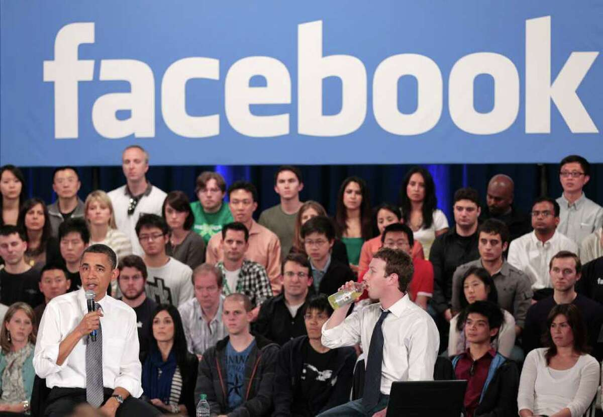 President Barack Obama, accompanied by Facebook CEO Mark Zuckerberg, speaks during a town hall meeting to discuss reducing the national debt, Wednesday, April 20, 2011, at Facebook headquarters in Palo Alto, Calif.