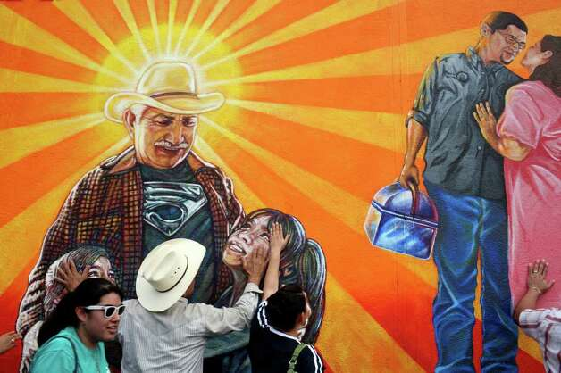 "Ricardo Luna, the father of orginal lead muralist Rigoberto Luna, hugs the part of the mural depicting himself embracing his granddaughters, next to his daughter-in-law, Victoria Barrientes-Luna,  during the rededication of the San Anto Cultural Arts' Community Mural/Public Art Program' Insomne de Amor"" on the side of a Kwik Wash laundromat in San Antonio on Saturday, August 16, 2008. The Priest asked all in attendance to hug with mural at the conclusion of the blessing of it. Victoria and her husband, Ruben, the son of Ricardo Luna, are depicted at right. Photo: Lisa Krantz, SAN ANTONIO EXPRESS-NEWS / SAN ANTONIO EXPRESS-NEWS"