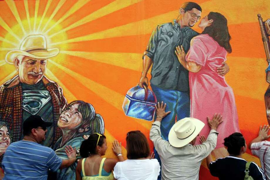 "At the urging of the Priest doing the Blessing of the Mural, family, including Ricardo Luna, right, who is depicted at left, friends and artists hug the mural during the rededication of the San Anto Cultural Arts' Community Mural/Public Art Program' Insomne de Amor"" on the side of a Kwik Wash laundromat in San Antonio on Saturday, August 16, 2008. Luna's son, Rigoberto Luna is the original lead muralist. Photo: Lisa Krantz, SAN ANTONIO EXPRESS-NEWS / SAN ANTONIO EXPRESS-NEWS"