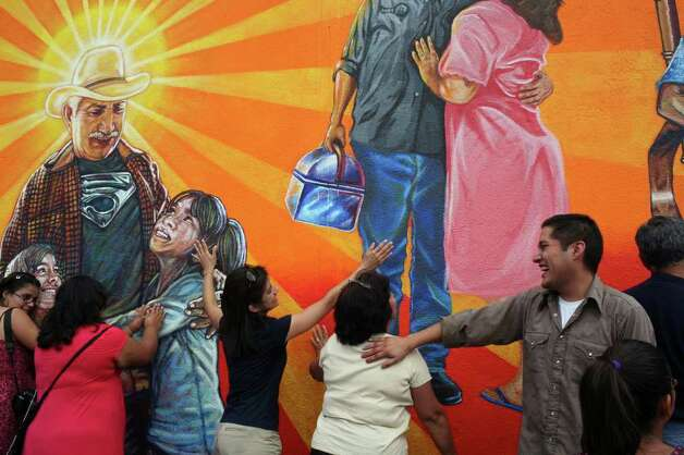 "Original Lead Muralist Rigoberto Luna, right, laughs with family and friends as they hug the mural at the urging of the Priest doing the Blessing of the Mural during the rededication of the San Anto Cultural Arts' Community Mural/Public Art Program' Insomne de Amor"" on the side of a Kwik Wash laundromat in San Antonio on Saturday, August 16, 2008. Photo: Lisa Krantz, SAN ANTONIO EXPRESS-NEWS / SAN ANTONIO EXPRESS-NEWS"