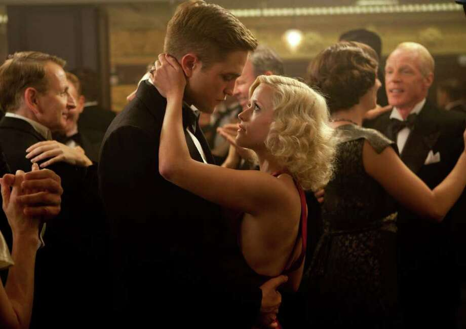 """In this publicity image released by Twentieth Century Fox, Robert Pattinson, left, and Reese Witherspoon are shown in a scene from """"Water for Elephants."""" (AP Photo/Twentieth Century Fox, David James) Photo: AP"""