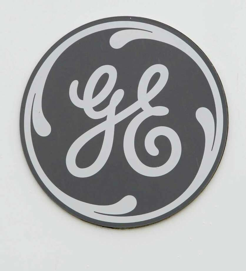 In this Tuesday, April 19, 2011 photo the General Electric logo is seen on a sign at the entrance to the aviation manufacturing plant in Lynn, Mass. GE said Thursday, April 21, earnings jumped 77 percent in the first quarter, led by strong results in its financial services business.  (AP Photo/Steven Senne) Photo: Steven Senne