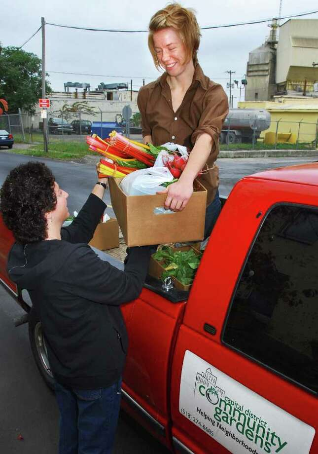 Capital District Community Gardens helps fill a need for fresh produce with plenty of help from gardeners. Amy Klein, left, and Sara Warden load donations for delivery in 2006. (Times Union archive) Photo: John Carl D'Annibale / Albany Times Union