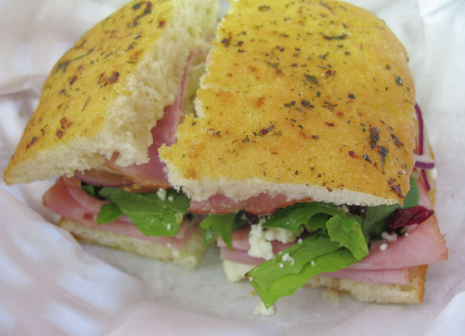 The Pacific sandwich is served with ham, melted Havarti, pineapple, cranberries, feta cheese, mayo and mixed greens on focaccia bread. JENNIFER McINNIS / EXPRESS-NEWS